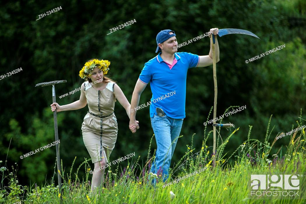 Stock Photo: Young couple with an agricultural tool in the field.