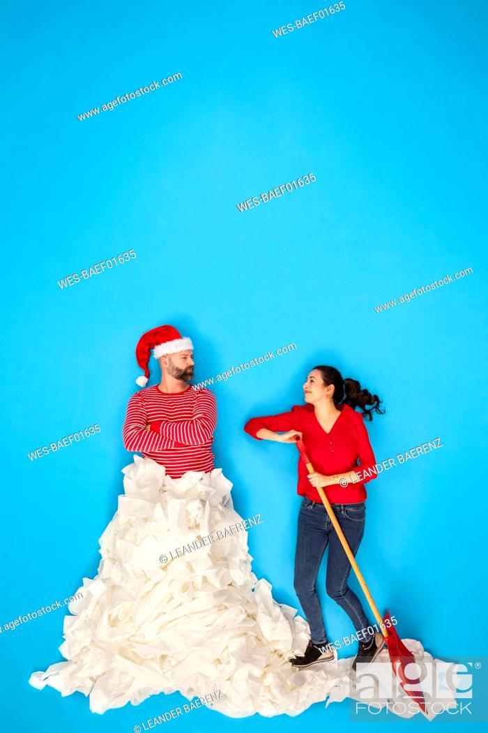 Stock Photo: Couple shoveling snow, man wearing Santa hat.