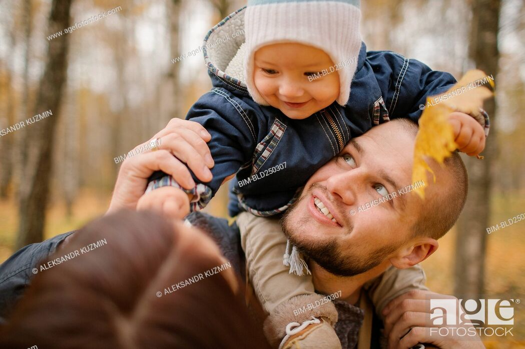 Stock Photo: Middle Eastern father carrying baby son in autumn.
