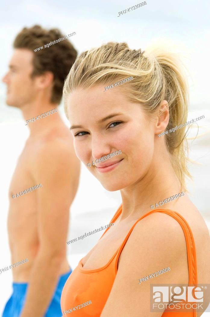 Stock Photo: Portrait of a woman standing with a man on the beach.