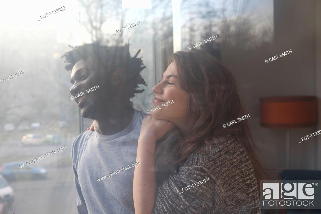Stock Photo: An affectionate couple looking out a window.