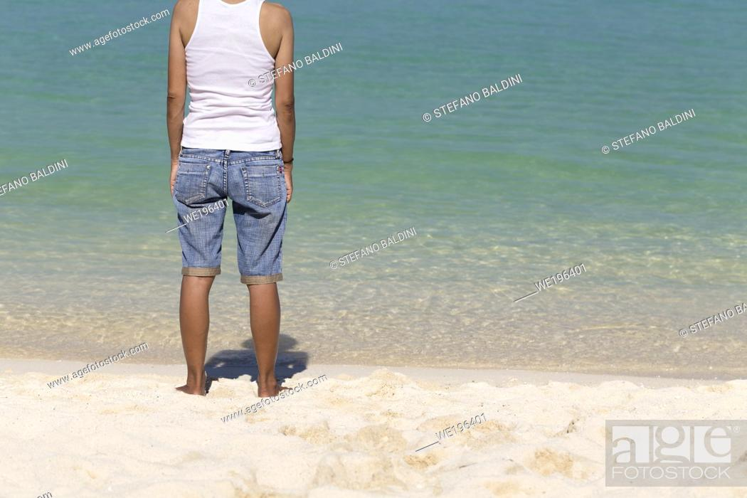 Imagen: Rear view of asian woman standing on the beach, Thailand.
