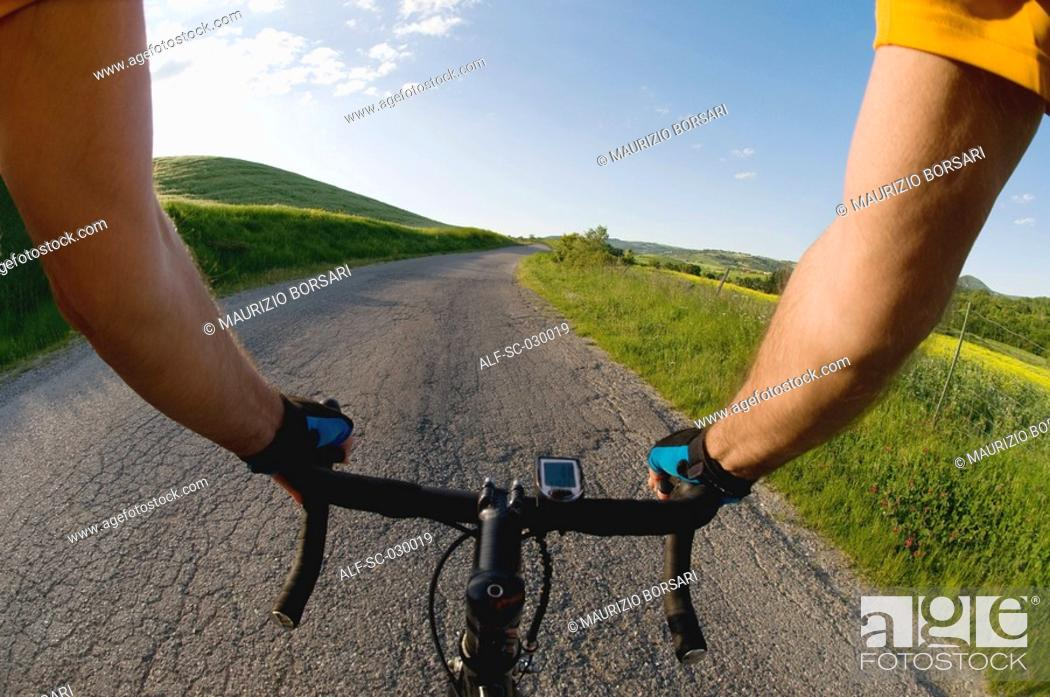 Stock Photo: Close-up view of hands on handle bars of a bicycle.