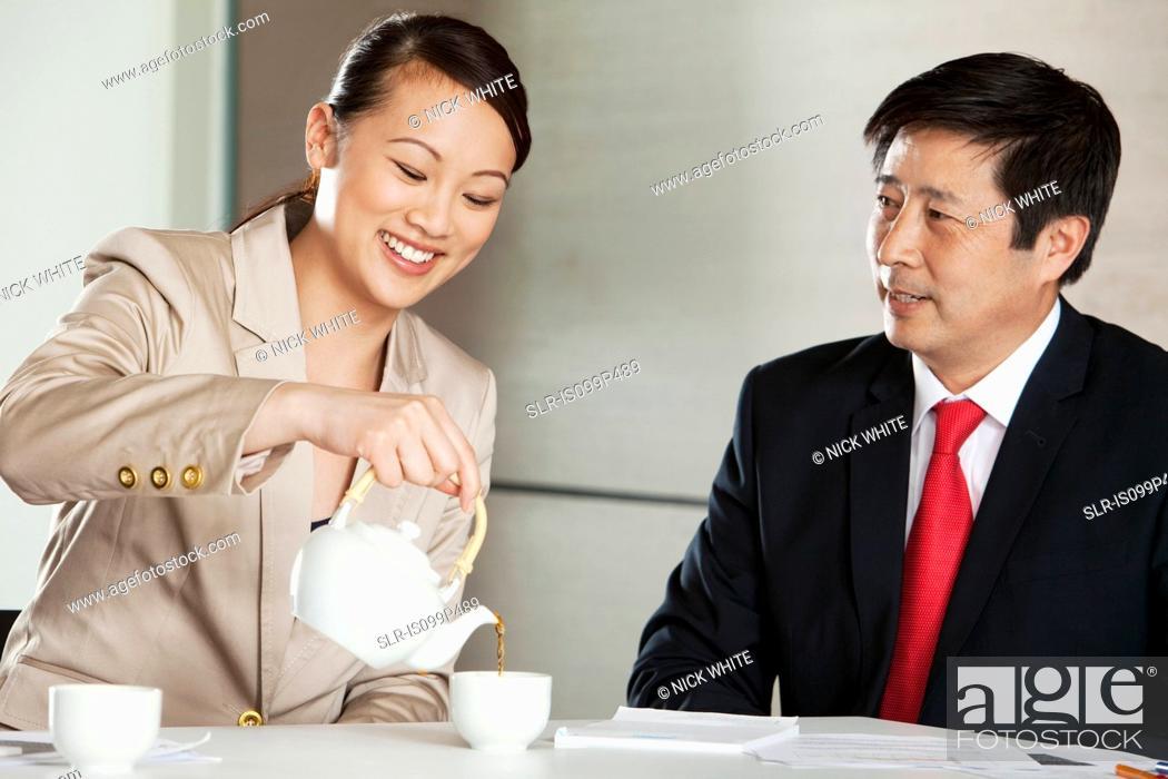 Stock Photo: Businesswoman pouring tea for businessman.