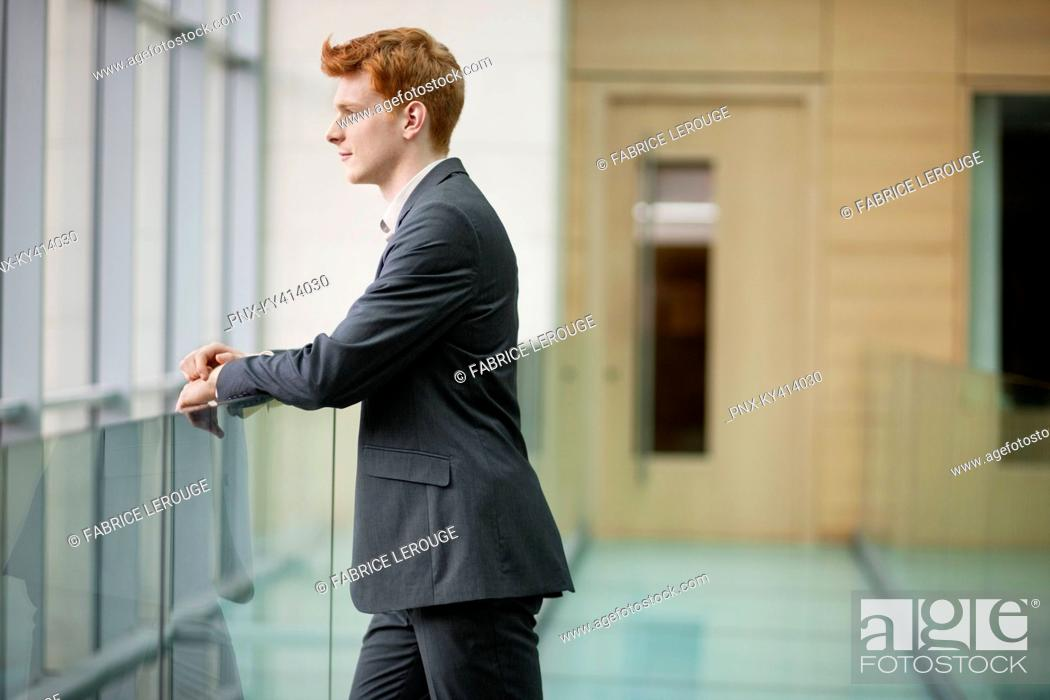 Stock Photo: Businessman looking through glass window in a corridor.