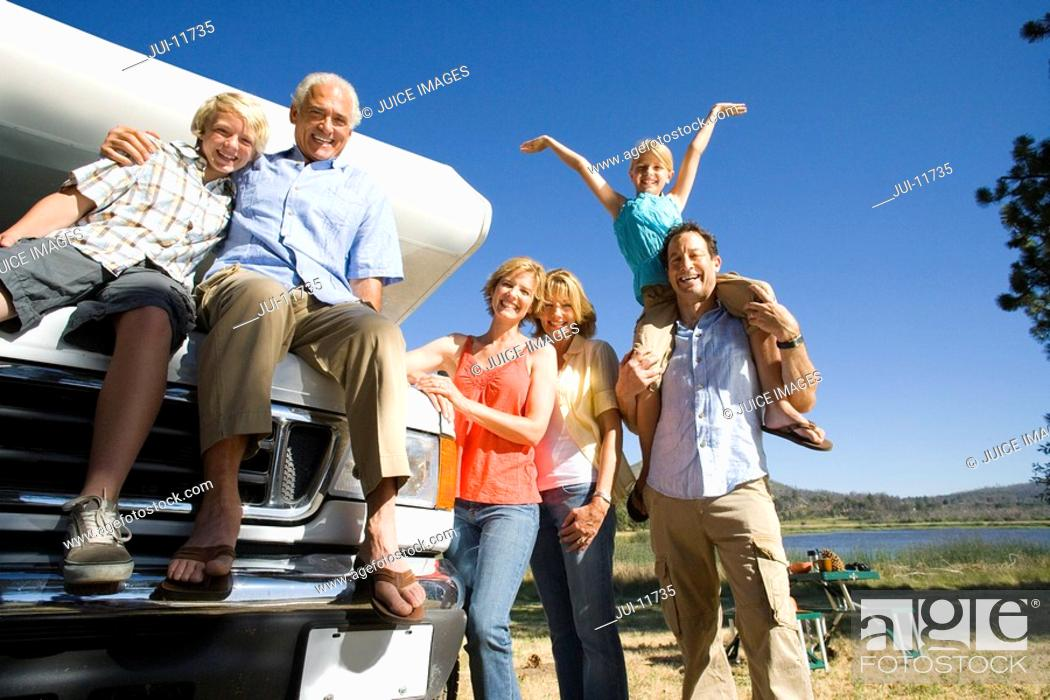 Stock Photo: Family of three generations by motor home and lake, smiling, portrait, low angle view.