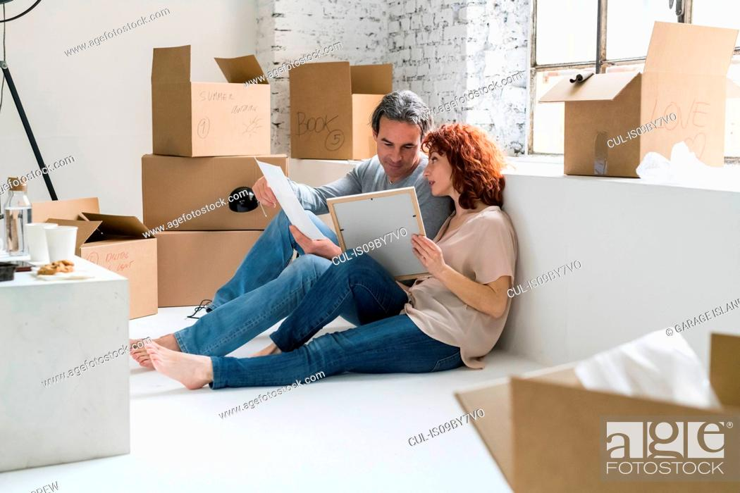 Stock Photo: Couple moving into industrial style apartment, sitting on floor looking at pictures.