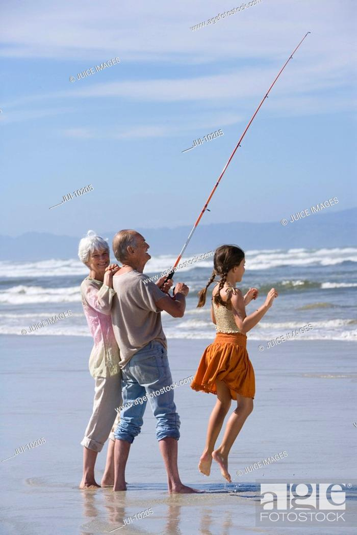Stock Photo: Girl 7-9 by grandparents fishing on beach, portrait of senior woman.