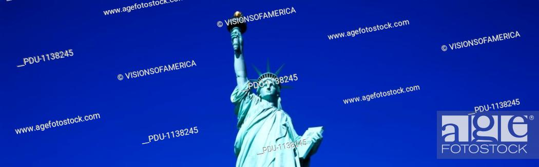 Stock Photo: This is the top half of the Statue of Liberty against a blue sky in horizontal format.