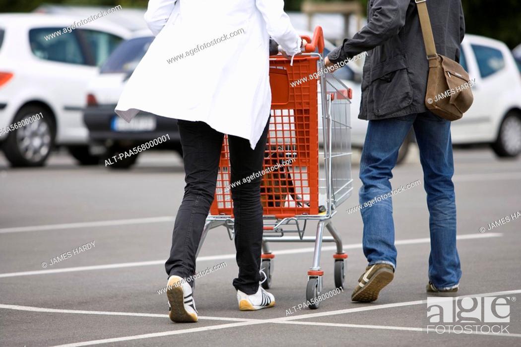 Stock Photo: Shoppers pushing shopping cart in parking lot.