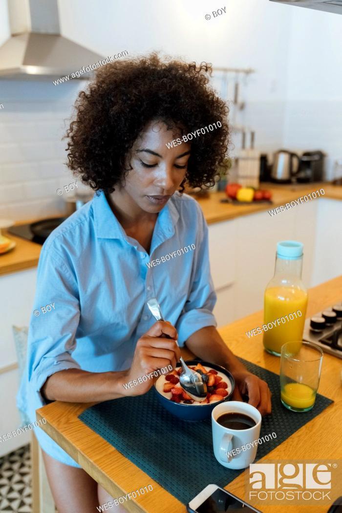 Stock Photo: Woman having breakfast in her kitchen, eating fruit.