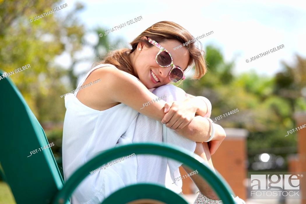 Stock Photo: A woman sitting on a park bench, smiling at the camera.