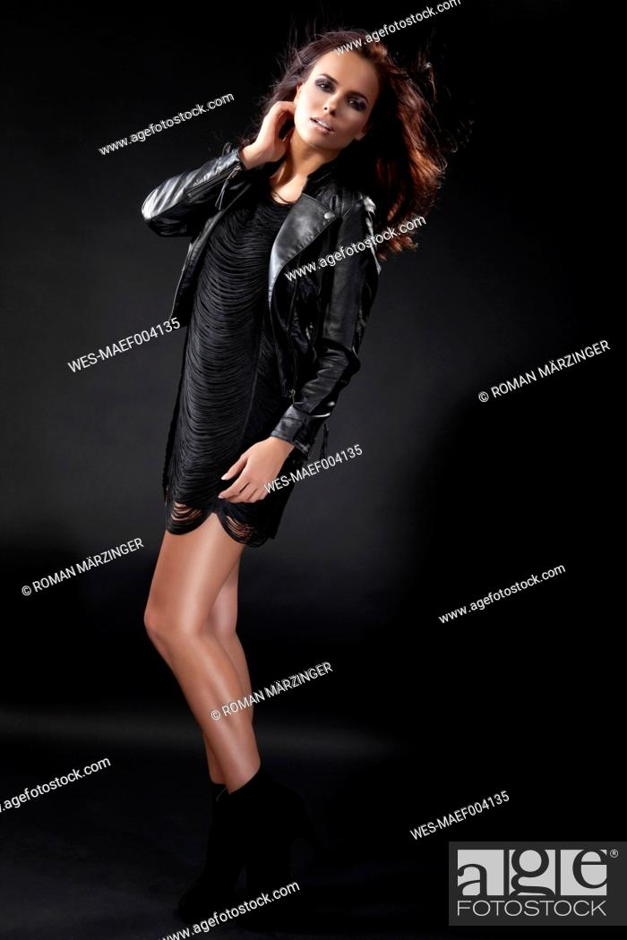 Stock Photo: Young woman in black dress and leather jacket, portrait.