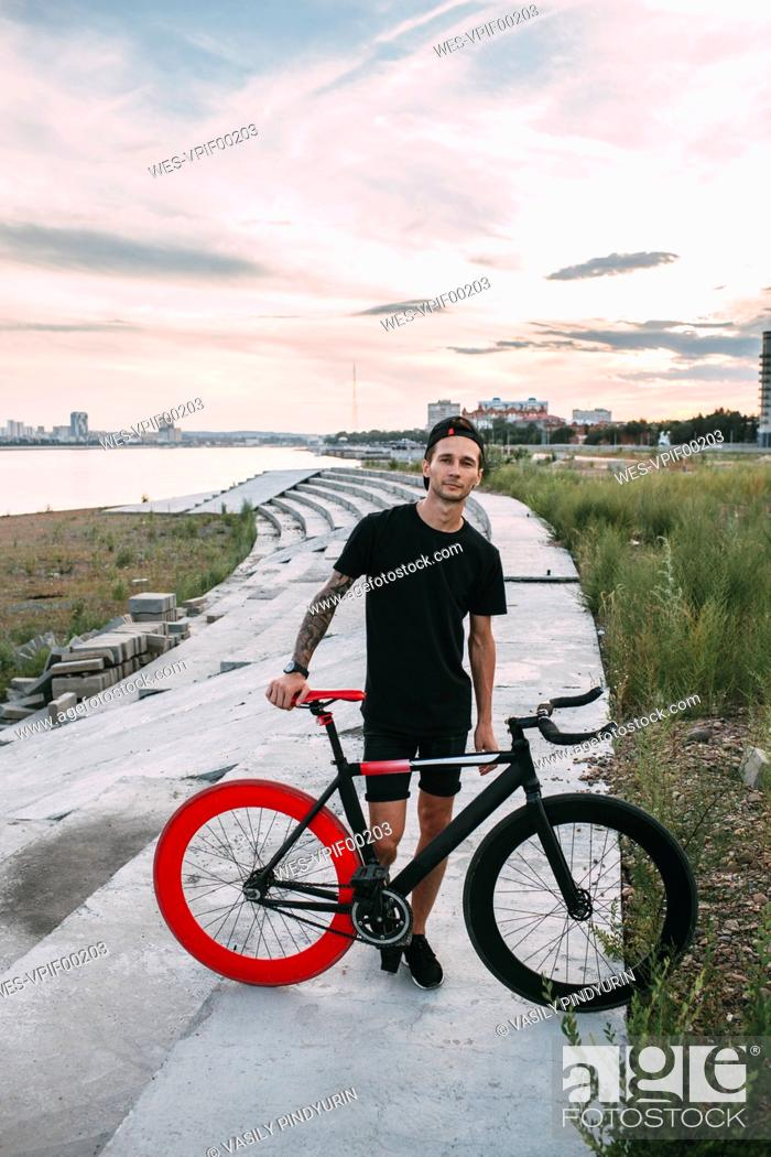 Stock Photo: Portrait of young man with fixie bike at sunset.