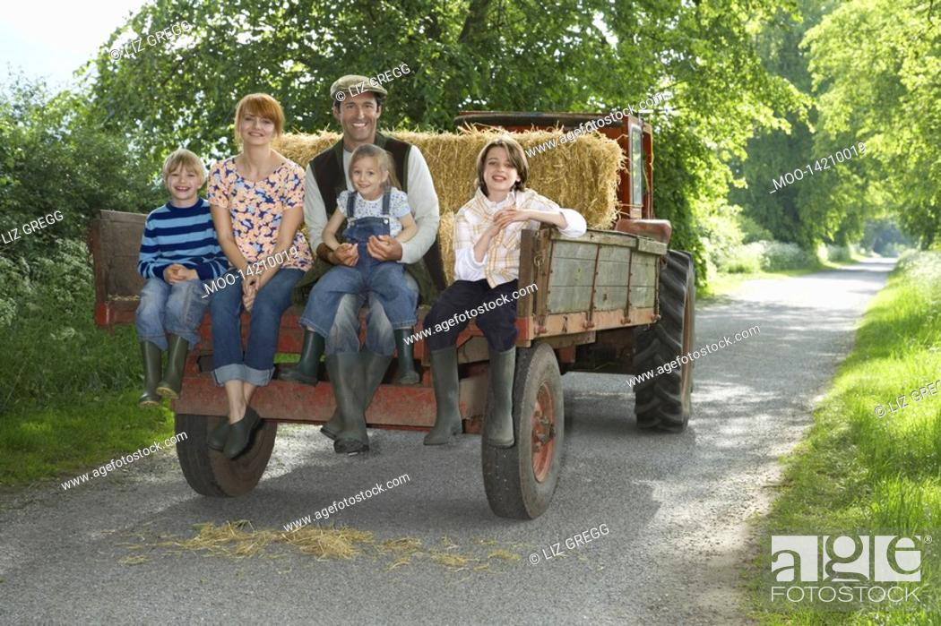 Stock Photo: Parents with three children 5-9 sitting on trailer on country lane portrait.