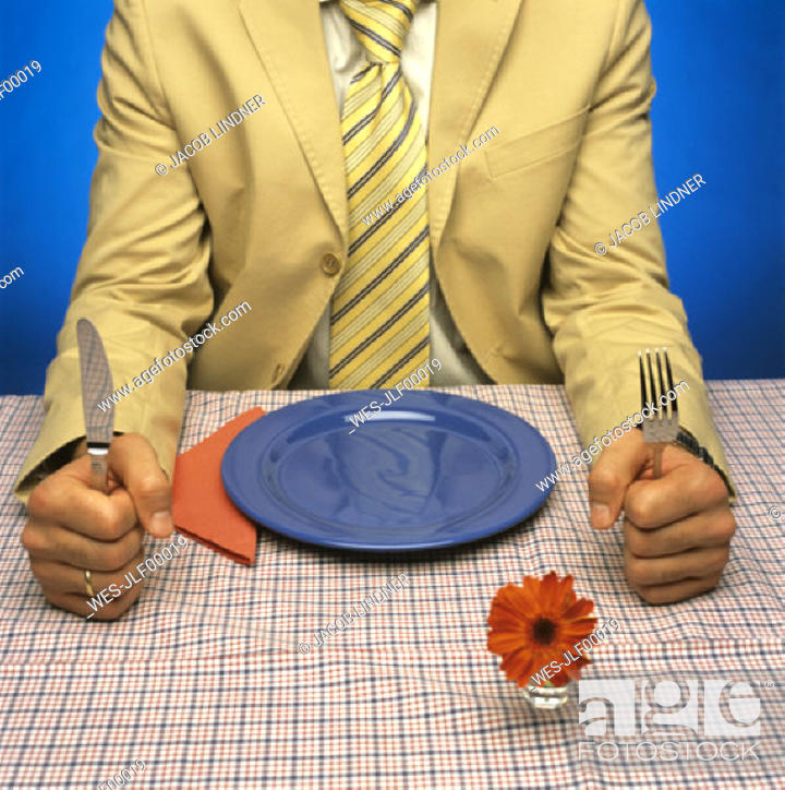 Stock Photo: Man sitting at table with empty plate, holding cutlery.