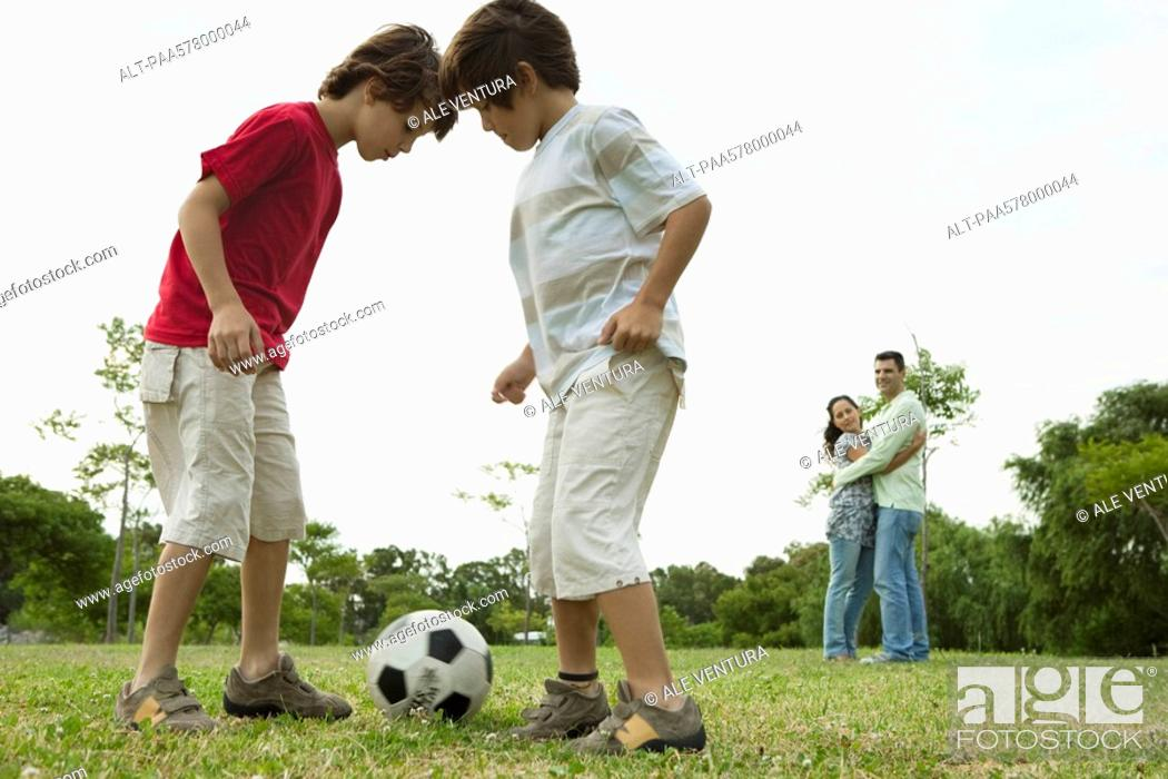 Stock Photo: Boys playing soccer, parents embracing in background.