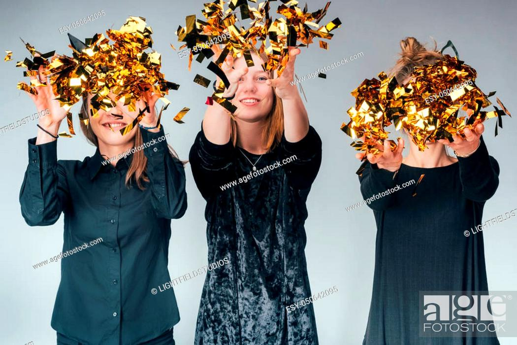 Stock Photo: group of young women throwing up golden confetti, isolated on grey.