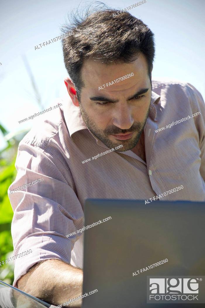 Imagen: Man using laptop computer outdoors.