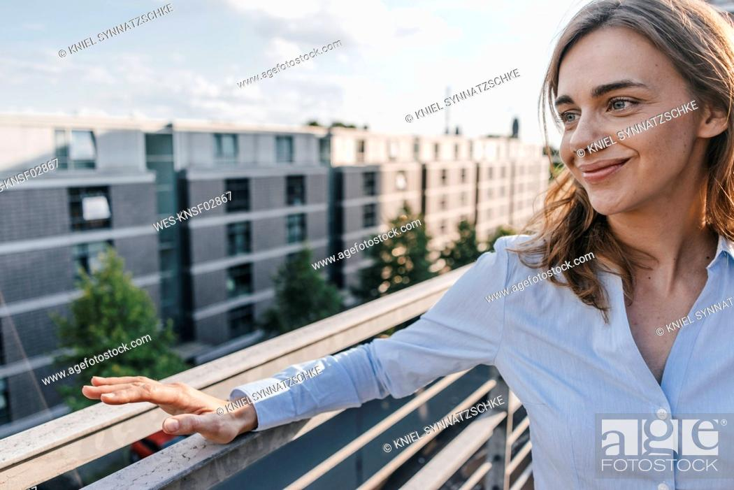 Stock Photo: Businesswoman standing on terrace of industrial building.