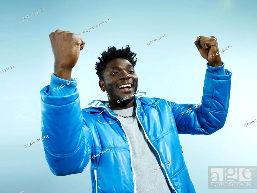 Stock Photo: A young hip man with his arms raised in celebration.