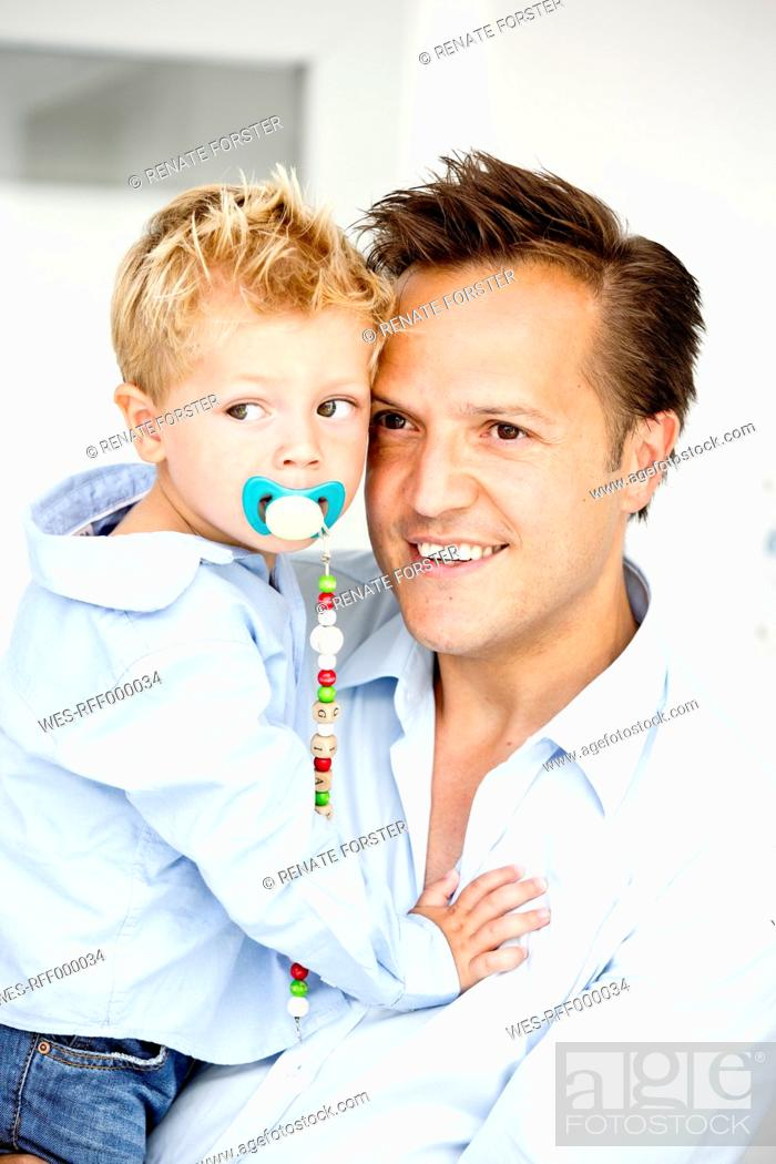 Stock Photo: Germany, Son carrying pacifier, close-up.