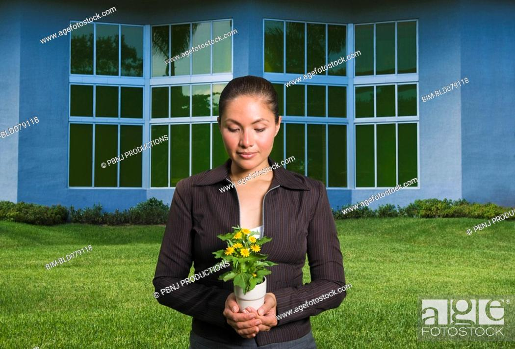 Stock Photo: Mixed race woman holding flowers in pot.