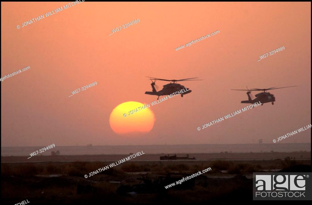 Stock Photo: IRAQ -- 02 Apr 2003 -- Army HH-60 Blackhawk helicopters fly past the setting sun at an air base in southern Iraq. USAF photo -- Picture by Shane A Cuomo / USAF.