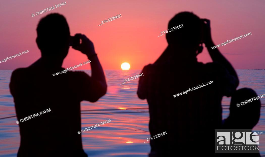Stock Photo: Photographing sunrise. Dolphin watch sunrise tour, Cala Ratjada, Mallorca, Balearic islands, Spain in July.