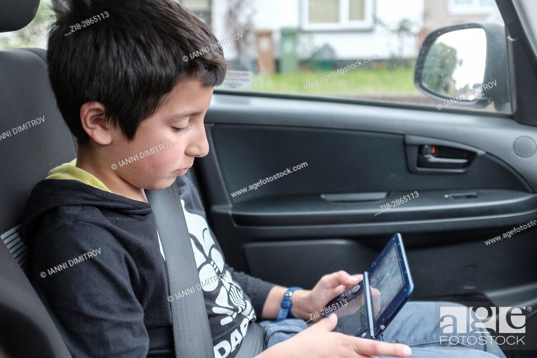 Stock Photo: Boy, 10 years old, plays computer game in car, UK.