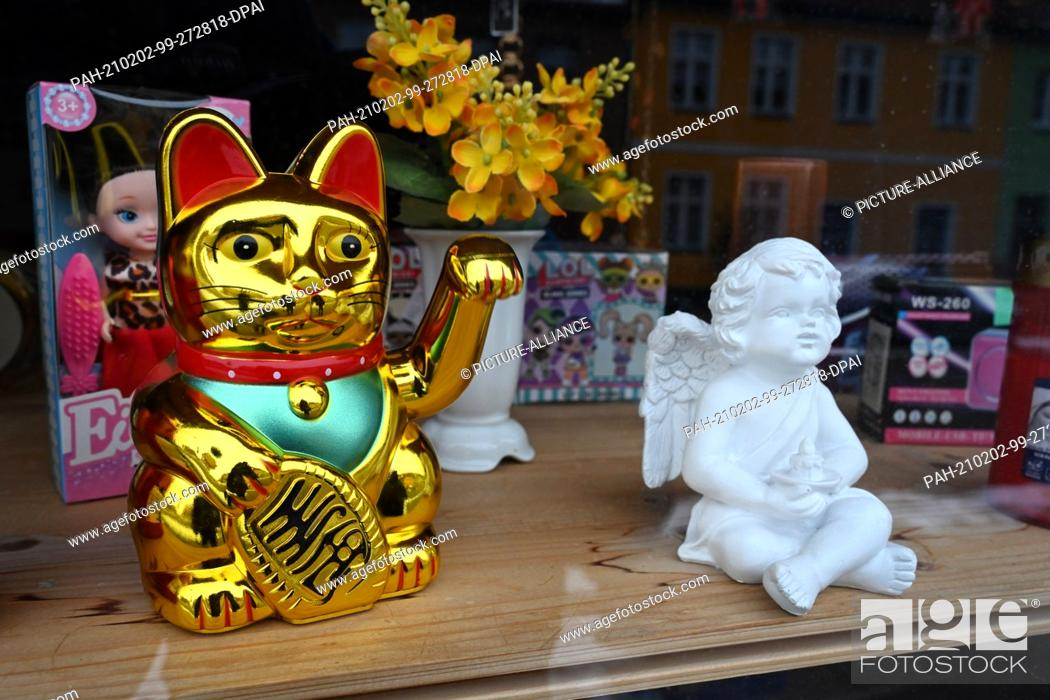 Stock Photo: 01 February 2021, Mecklenburg-Western Pomerania, Loitz: A Maneki Neko gold waving cat stands in a shop window in the town centre of Loitz in the district of.
