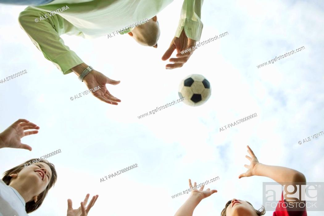 Stock Photo: Father and sons playing with soccer ball, low angle view.