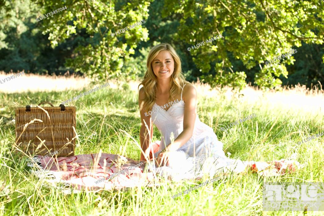 Stock Photo: A young woman sitting on a picnic blanket.