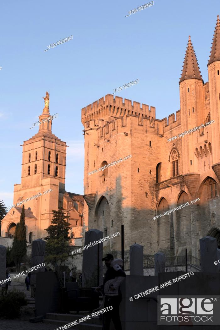 Imagen: The pink lit forms of the papal palace pinnacles and towers and the golden madonna of the cathedral are repeated below in the grey clad cafe parasols, Avignon.
