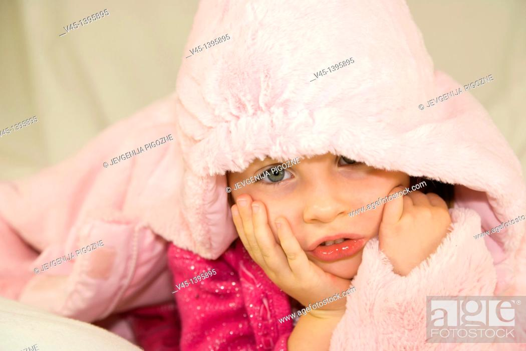 Stock Photo: 4 years old girl in pink clothing lying under the hood.