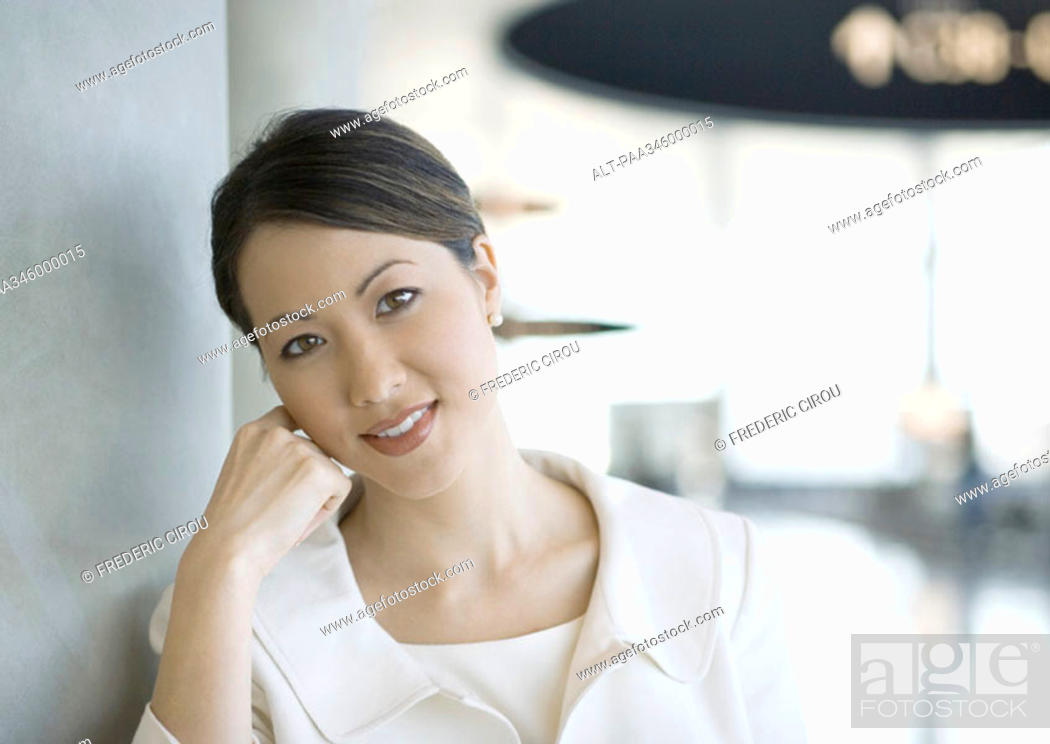 Stock Photo: Female traveler leaning head on hand in airport, smiling at camera.