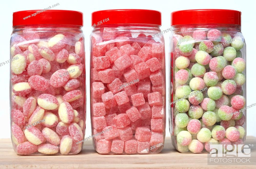 Stock Photo: jars containers of traditional british sweets candies including rhubarb and custard cola cubes and rosey apples in the uk.
