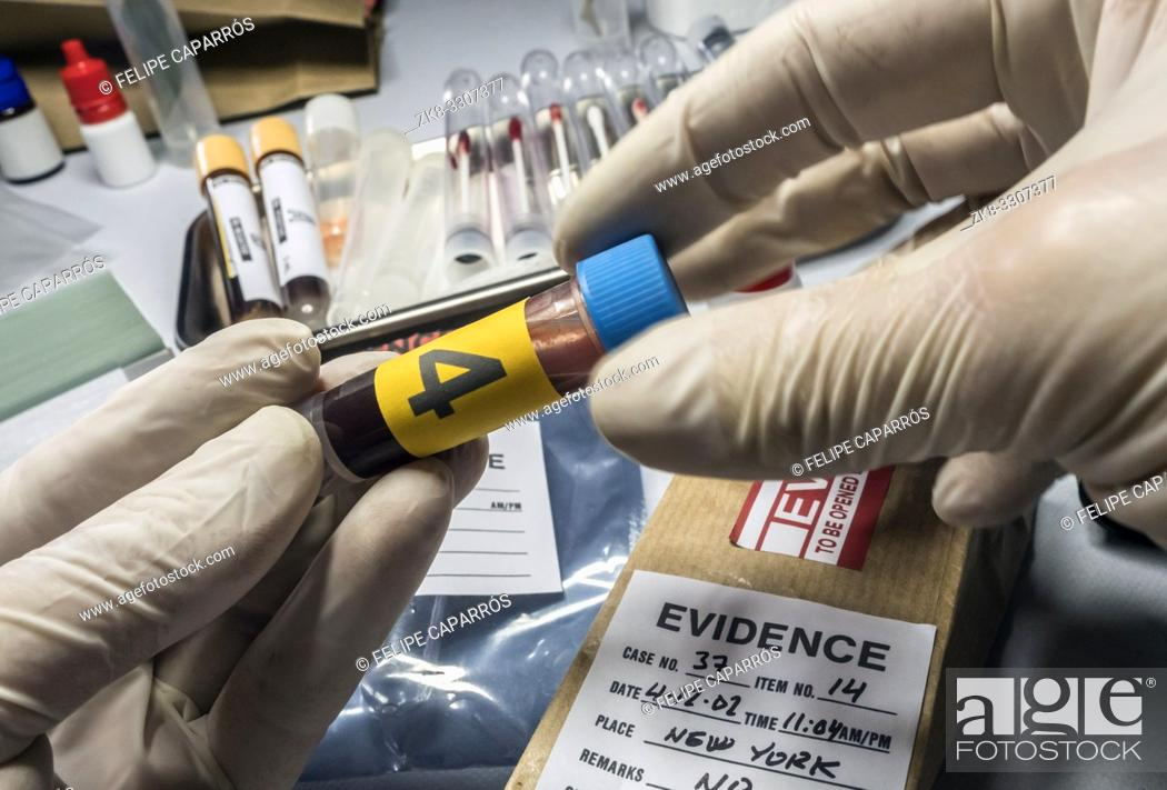 Stock Photo: Police expert gets blood sample from glass bottle in Criminalistic Lab, conceptual image.