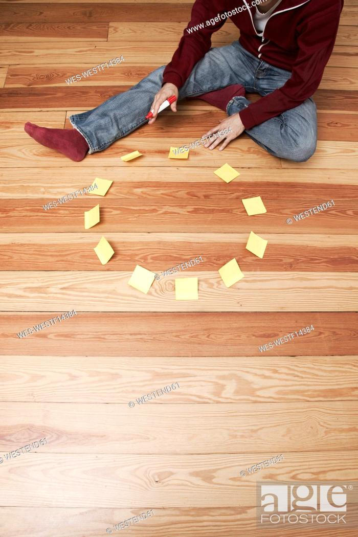 Stock Photo: Man sitting besides a circle of adhesive notes.