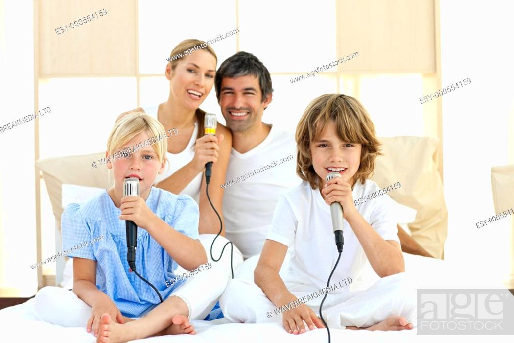 Stock Photo: Jolly family singing together through microphones.