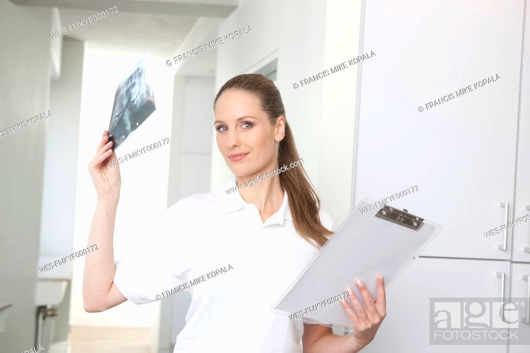 Stock Photo: Germany, Dentist looking at dental x-rays.