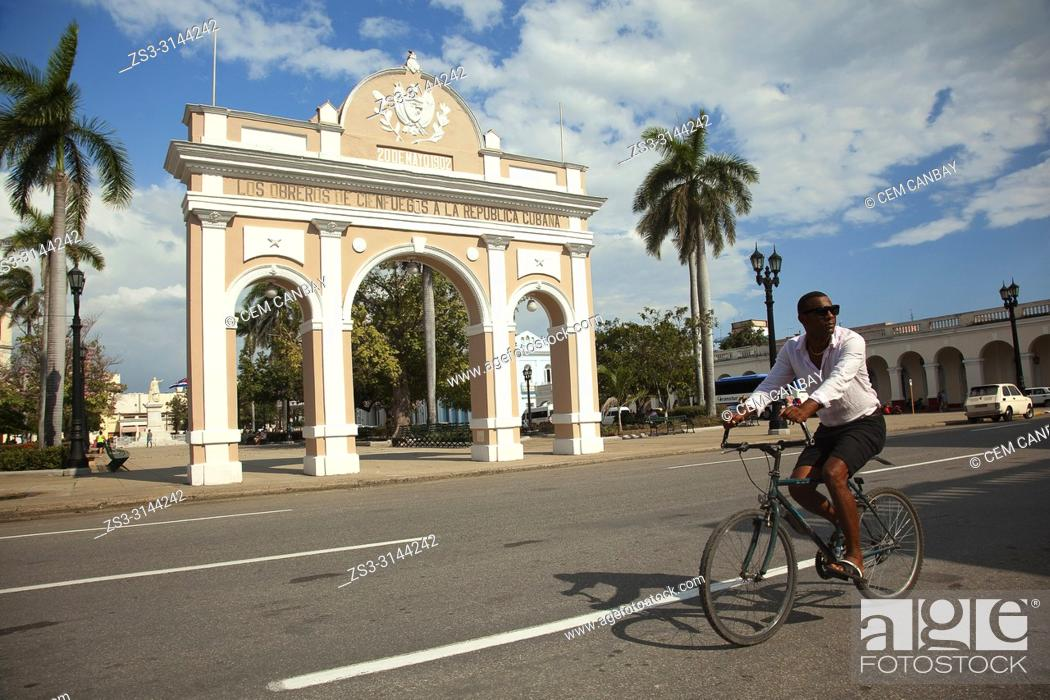 Imagen: Cyclist in front of the Triumphal Arch-Arco de Triunfo in Jose Marti Park-Parque Jose Marti, Cienfuegos, Cienfuegos Province, Cuba, West Indies, Central America.