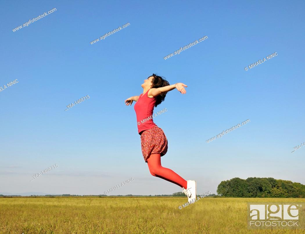 Stock Photo: Young woman jumping in air.