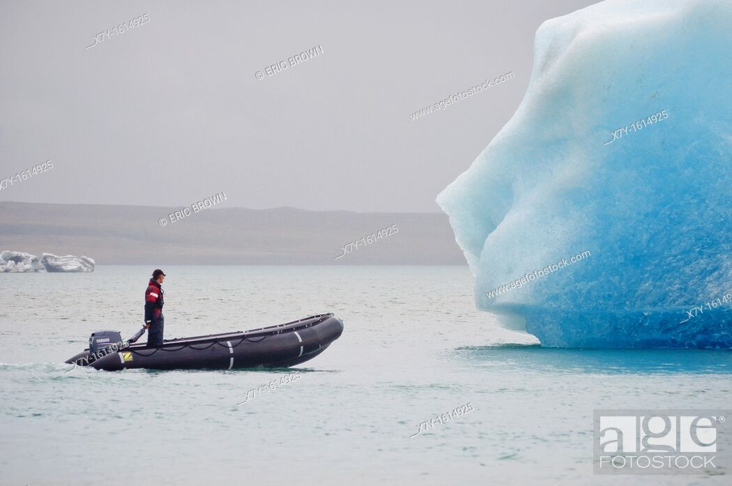 Stock Photo: A man in a raft approaches an iceberg in Glacier Lagoon, Iceland.