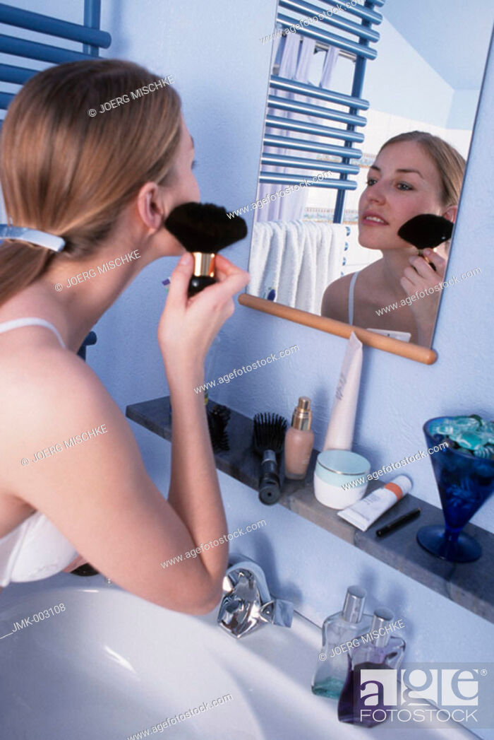 Stock Photo: A young woman, 20-25 25-30 years old, in the bathroom, putting powder on her face in front of a mirror.