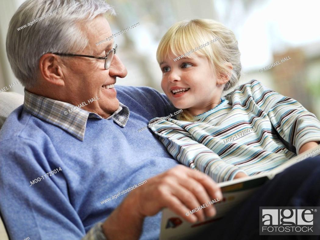 Stock Photo: Grandfather reading to girl 3-4 close-up.