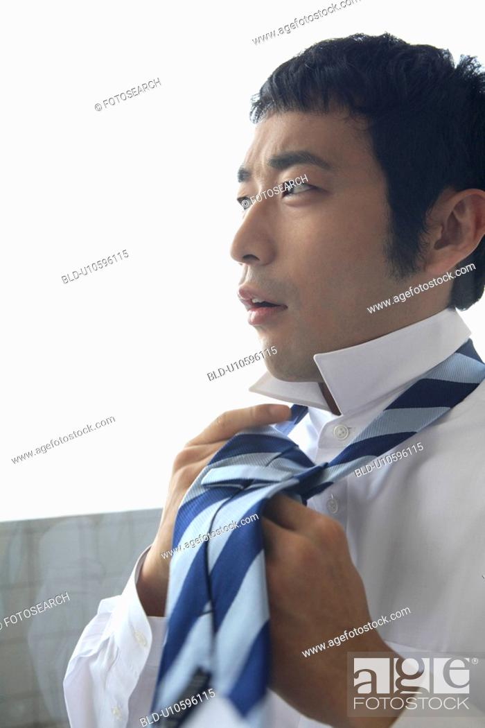 Stock Photo: Businessman putting on a tie.