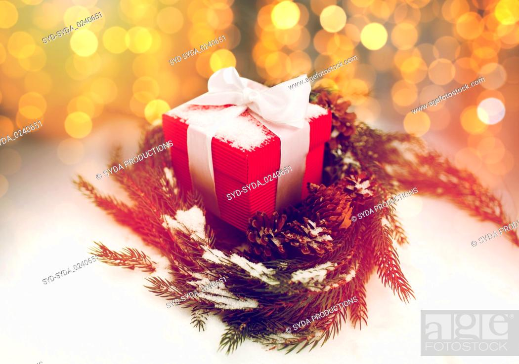 Stock Photo: christmas gift and fir wreath with cones on snow.