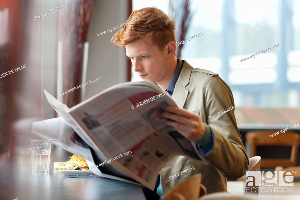 Stock Photo: Man sitting in a restaurant and reading a newspaper.
