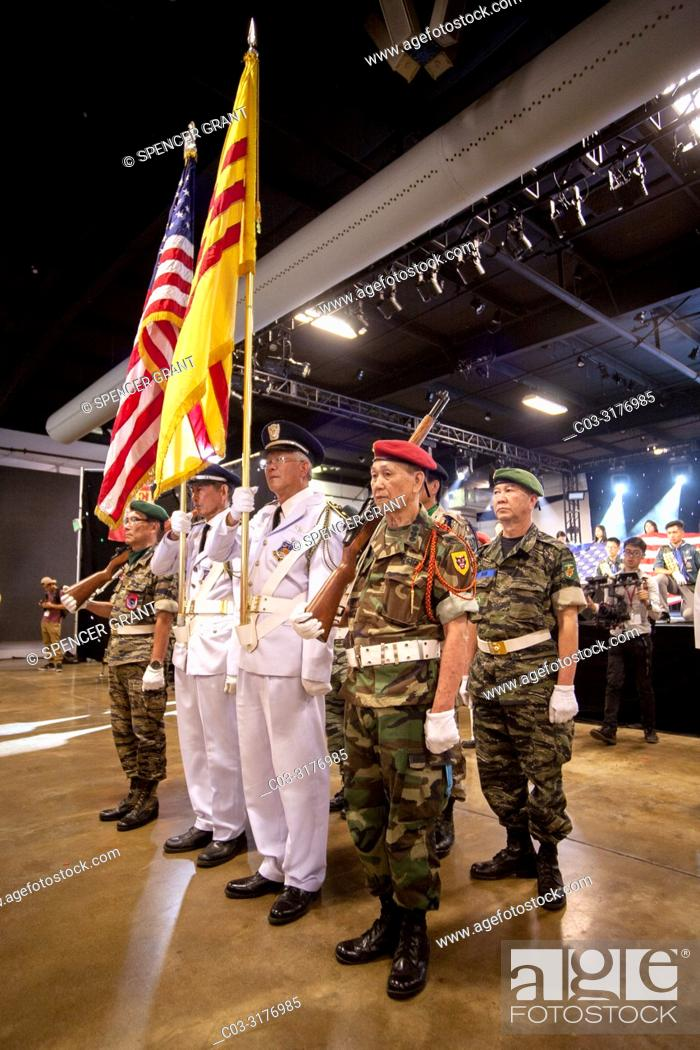 Carrying Vietnamese and American flags, an honor guard of former